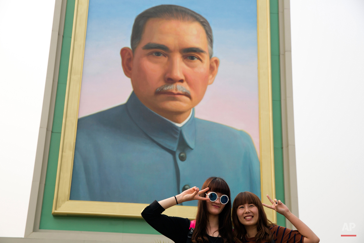 Visitors pose for photos near a portrait of Sun Yat-sen, who is widely regarded as the founding father of modern China, displayed for the May Day holidays on Tiananmen Square in Beijing Friday, May 1, 2015. Millions of Chinese are taking advantage of the May Day holidays to visit popular tourist sites. (AP Photo/Ng Han Guan)