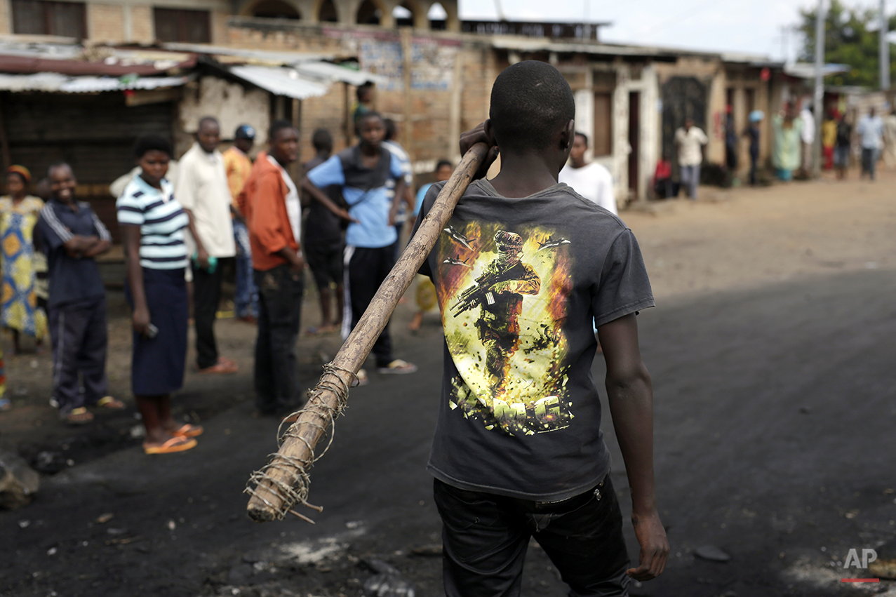 A demonstrator carrying a stick walks in the Musaga neighborhood of Bujumbura, Burundi, Friday May 1, 2015. Anti-government street demonstrations continued for a sixth day in protest against the move by President Pierre Nkurunziza to seek a third term. (AP Photo/Jerome Delay)