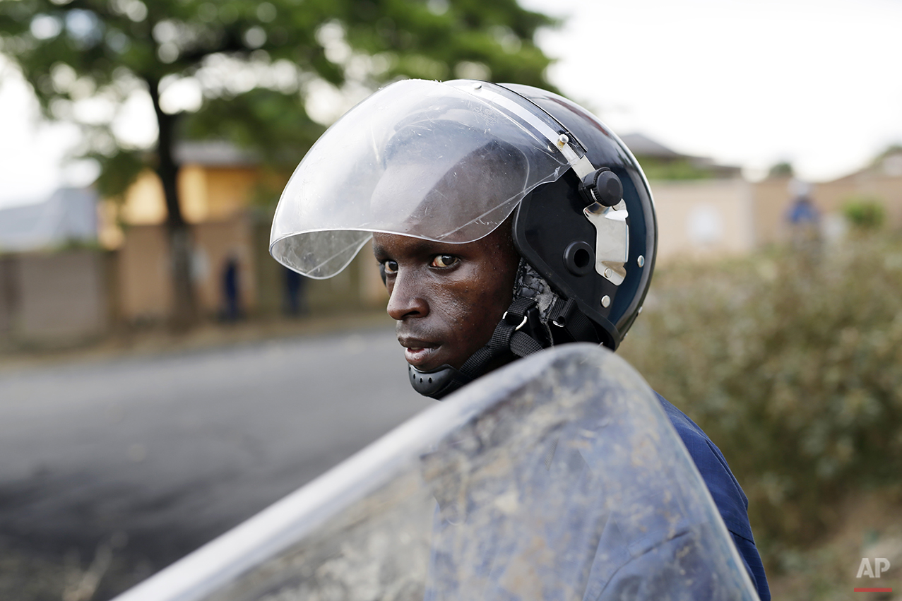 A Burundi riot police officer watches a group of stone throwing demonstrators during clashes in the Musaga district of Bujumbura, Burundi, Tuesday April 28, 2015. Anti-government street demonstrations continued for a third day after six people died in protests against the move by President Pierre Nkurunziza to seek a third term. (AP Photo/Jerome Delay)