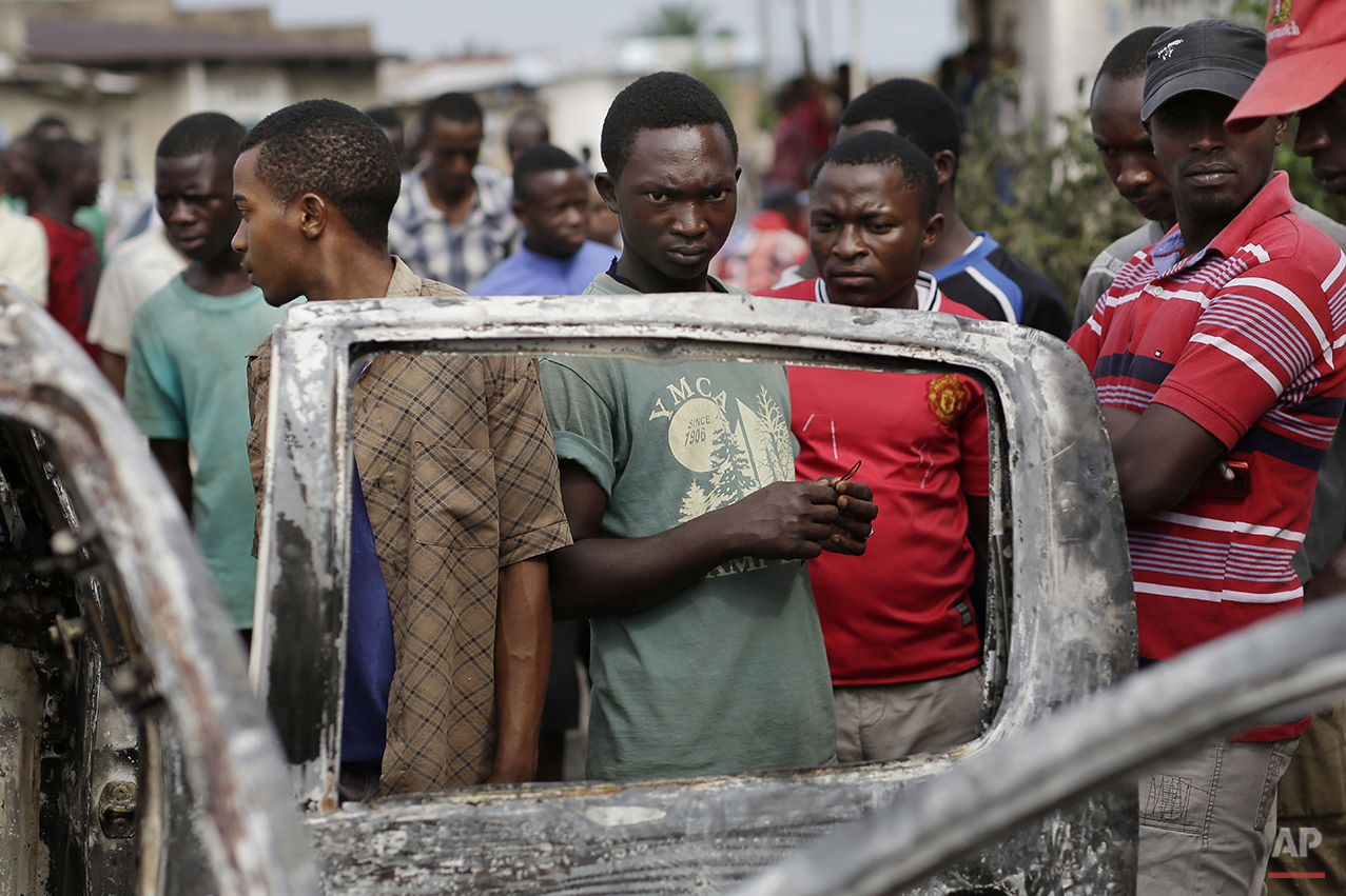 Residents of the Musaga neighborhood stand by the burnt out remains of a car in Bujumbura, Burundi, Friday May 1, 2015. Anti-government street demonstrations continued for a sixth day after in protests against the move by President Pierre Nkurunziza to seek a third term. (AP Photo/Jerome Delay)