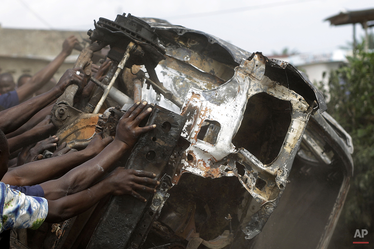 Demonstrators topple a burnt out car in the Musaga neighborhood of Bujumbura, Burundi, Friday May 1, 2015. Anti-government street demonstrations continued for a sixth day in protest against the move by President Pierre Nkurunziza to seek a third term in office. (AP Photo/Jerome Delay)