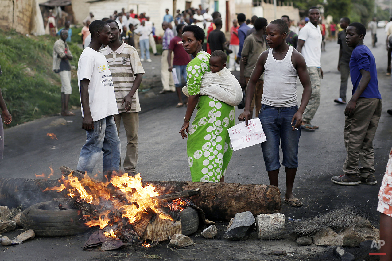 A woman carrying her baby joins demonstrators on a barricade during clashes in Bujumbura, Burundi, Wednesday April 29, 2015. Protesters were again on the streets Wednesday, angry over the Burundian president's third term bid that they say is unconstitutional as a top U.S. diplomat headed to the East African nation. (AP Photo/Jerome Delay)