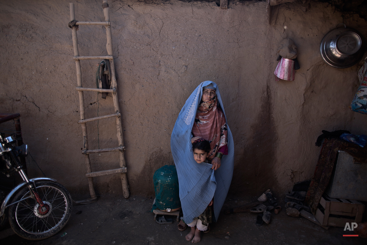In this Sunday, March 30, 2014, photo, Afghan refugee, Aziza Nazar, 37, a mother of 7 children, poses for a picture with her daughter Lal Mina, 3 at her neighbor's mud house, in a slum on the outskirts of Islamabad, Pakistan. (Muhammed Muheisen/AP for Time Magazine)