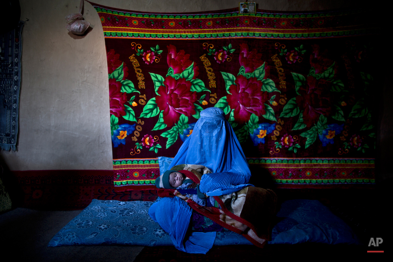 In this Saturday, March 29, 2014, photo, Afghan refugee, Gul Shireen Abdul, 40, a mother of 3 children, holds her daughter Zamina, 40 days, while posing for a picture at her mud house, in a slum on the outskirts of Islamabad, Pakistan. (Muhammed Muheisen/AP for Time Magazine)