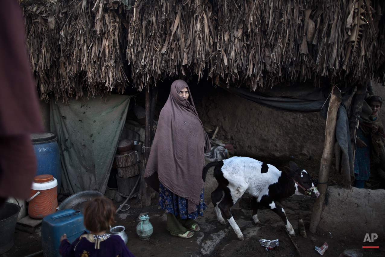In this Saturday, March 29, 2014, photo, Torbakey Haidar, 45, an Afghan refugee mother of 7 children, poses for a picture at her mud house in a slum on the outskirts of Islamabad, Pakistan. (Muhammed Muheisen/AP for Time Magazine)