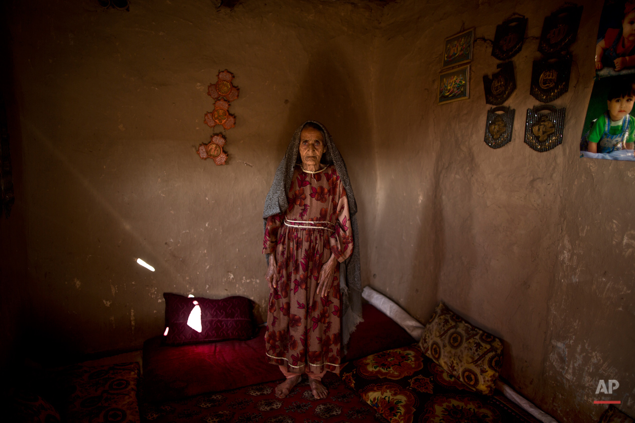 In this Monday, March 31, 2014, photo, Afghan refugee, Samar Gul, 89, a mother of 5 adults, poses for a picture at her mud house, on the outskirts of Islamabad, Pakistan.(Muhammed Muheisen/AP for Time Magazine)