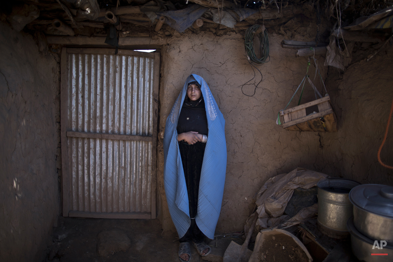 In this Sunday, March 30, 2014, photo, Afghan refugee, Fareeda Abdulgafour, 20, a mother of one child, poses for a picture at her mud house, in a slum on the outskirts of Islamabad, Pakistan. (Muhammed Muheisen/AP for Time Magazine)