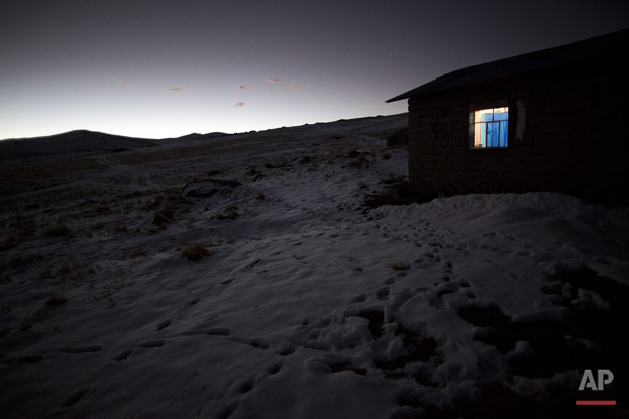 In this July 9, 2016 photo, light shines from a home's window in the late afternoon amid fields of snow in San Antonio de Putina in the Puno region of Peru, an area where locals raise alpaca and sheep for their wool. Every winter freeze destroys the tough grasslands the animals feed on and almost no crops can survive in the nutrient-poor soil. (AP Photo/Rodrigo Abd)