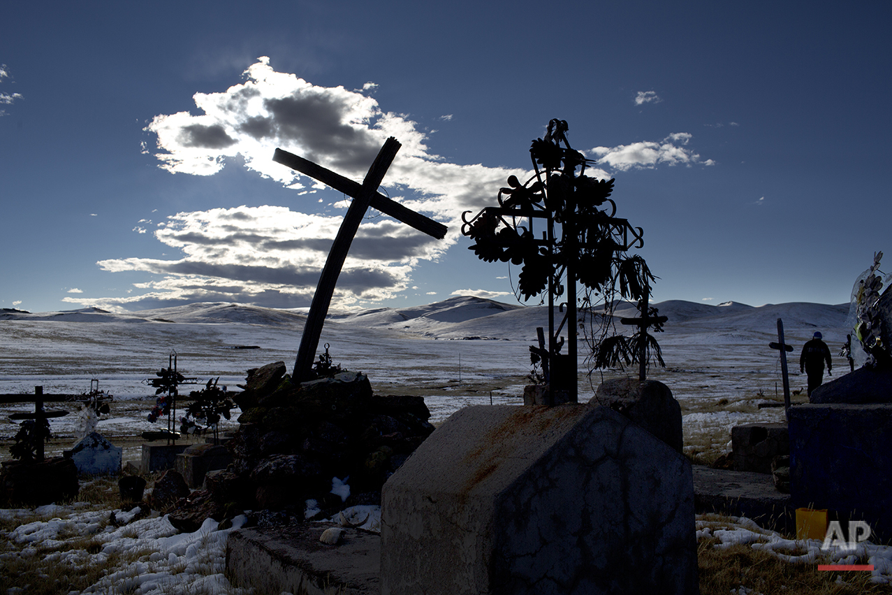 "In this July 9, 2016 photo, a cross stands in a snow covered cemetery in San Antonio de Putina in the Puno region of Peru, where people raise alpacas and sheep for their wool. ""Every year with the winter freezes and cold temperatures the plants and animals die,"" said Miguel Hadzich, head of a group affiliated with Peru's Catholic University that on its own has built 600 homes with heating for farmers. ""A scandal breaks out and then the state looks the other way. (AP Photo/Rodrigo Abd)"