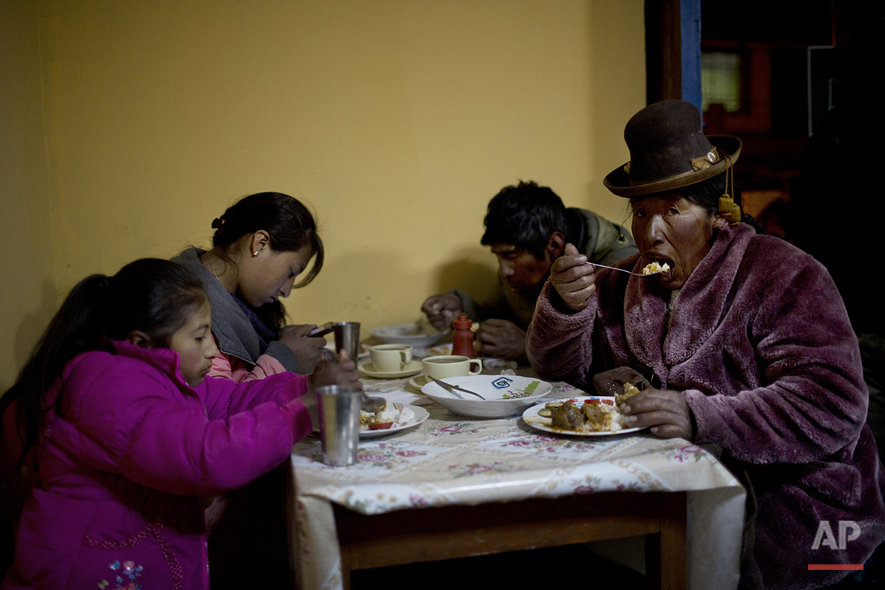 In this July 11, 2016 photo, villagers eat dinner at the town's only general store in San Antonio de Putina in the Puno region of Peru. Peru is the world's largest producer of alpaca wool, and the rural hamlets in this area is where the white-furred alpacas have been raised for centuries. (AP Photo/Rodrigo Abd)