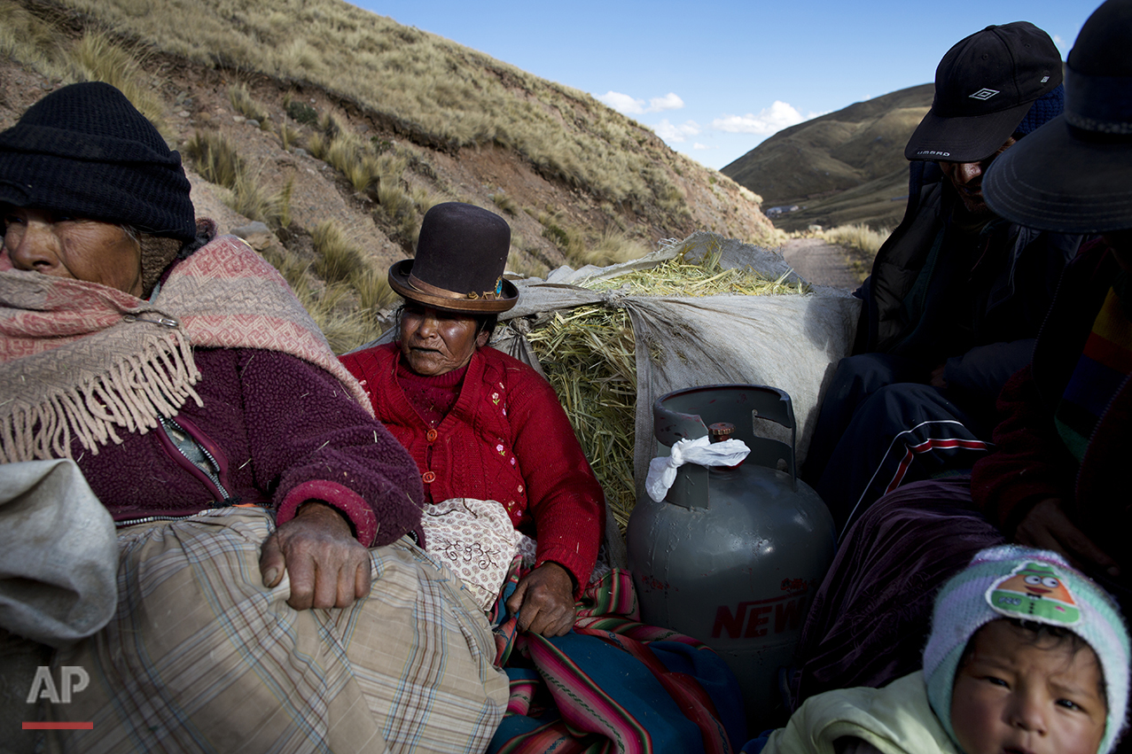 In this July 10, 2016 photo, camelid breeders ride in the back of a pick-up tuck with cooking gas and oats for their alpacas and sheep, as they return to their village of San Antonio de Putina in the Puno region of Peru. The passengers got the 30 minute ride from the nearest town of Cambria to their town from a friend since they don't own their own vehicle, the case of most locals. (AP Photo/Rodrigo Abd)