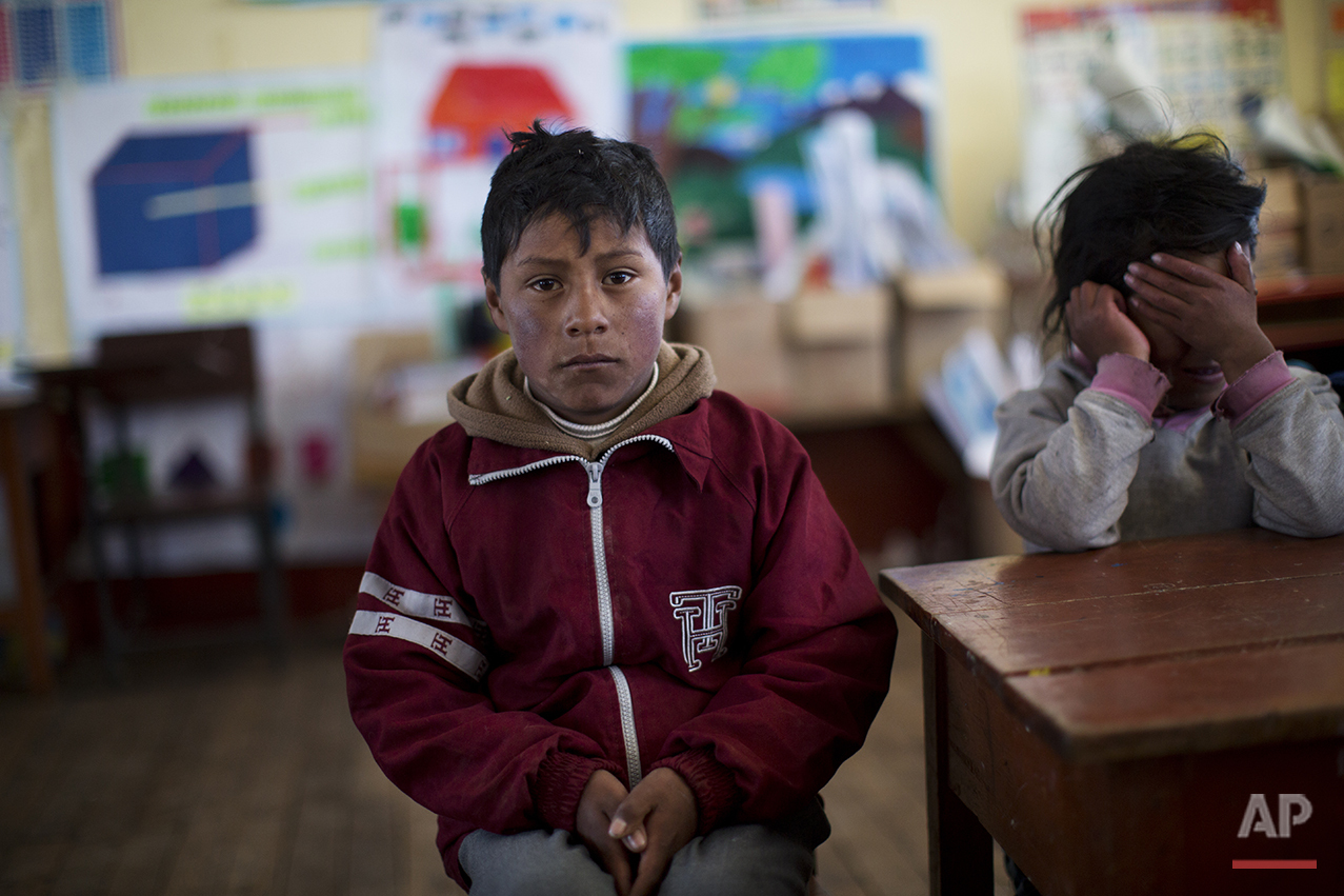 In this July 9, 2016 photo, a student waits for class to start at his public school in San Antonio de Putina in the Puno region of Peru. Due to the recent sub-freezing temperatures, the start of the school day has been delayed to 9am. (AP Photo/Rodrigo Abd)