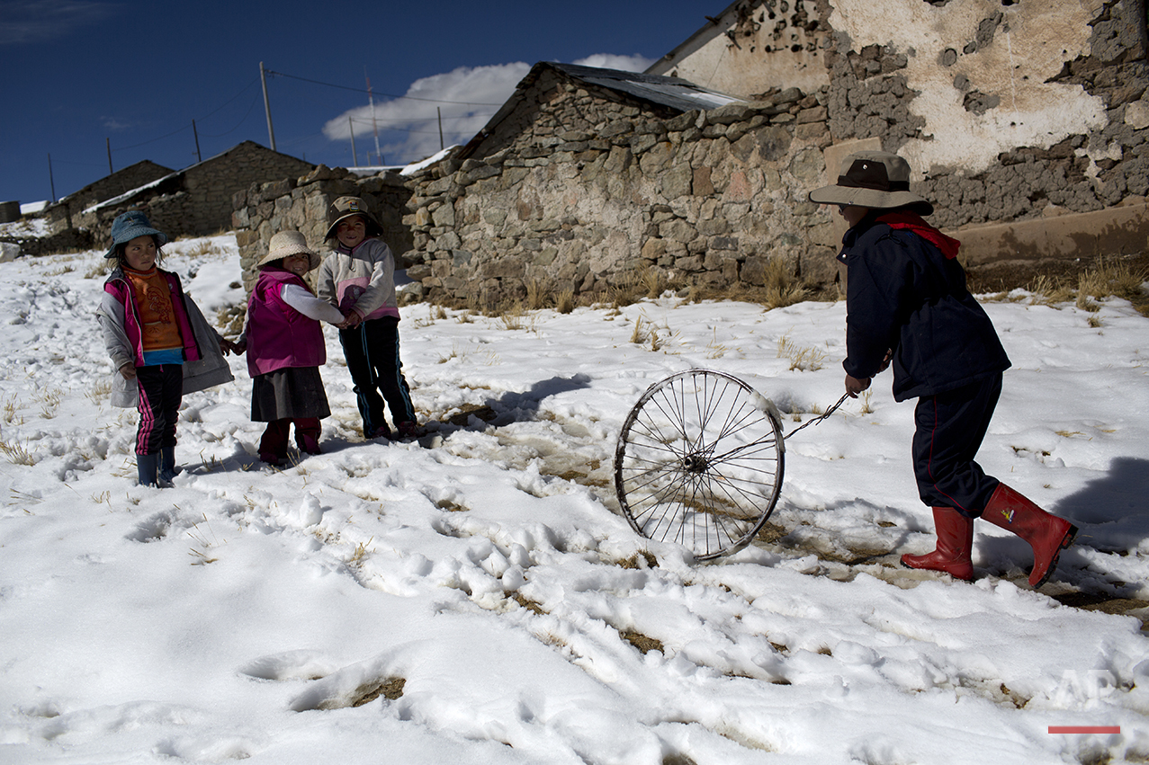 In this July 9, 2016 photo, children play after school in San Antonio de Putina in the Puno region of Peru. Two months into the cold season an estimated 14,000 children in the Andes have suffered from respiratory illnesses and 105 died, according to government figures. (AP Photo/Rodrigo Abd)