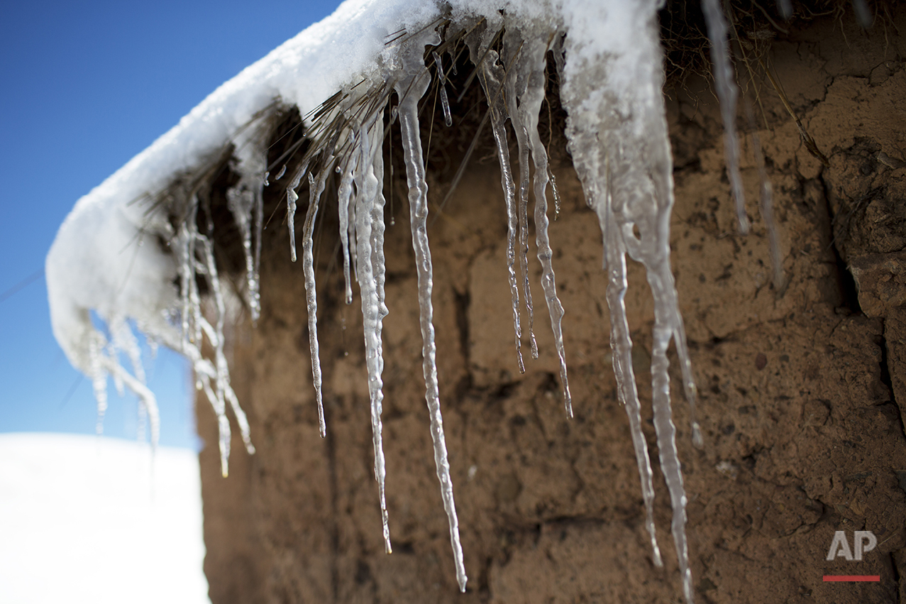 In this July 8, 2016 photo, icicles hang from the roof of an adobe home in San Antonio de Putina in the Puno region of Peru, where farmers raise alpacas and sheep for their wool. Every winter freeze destroys the tough grasslands the animals feed on and almost no crops can survive in the nutrient-poor soil. (AP Photo/Rodrigo Abd)