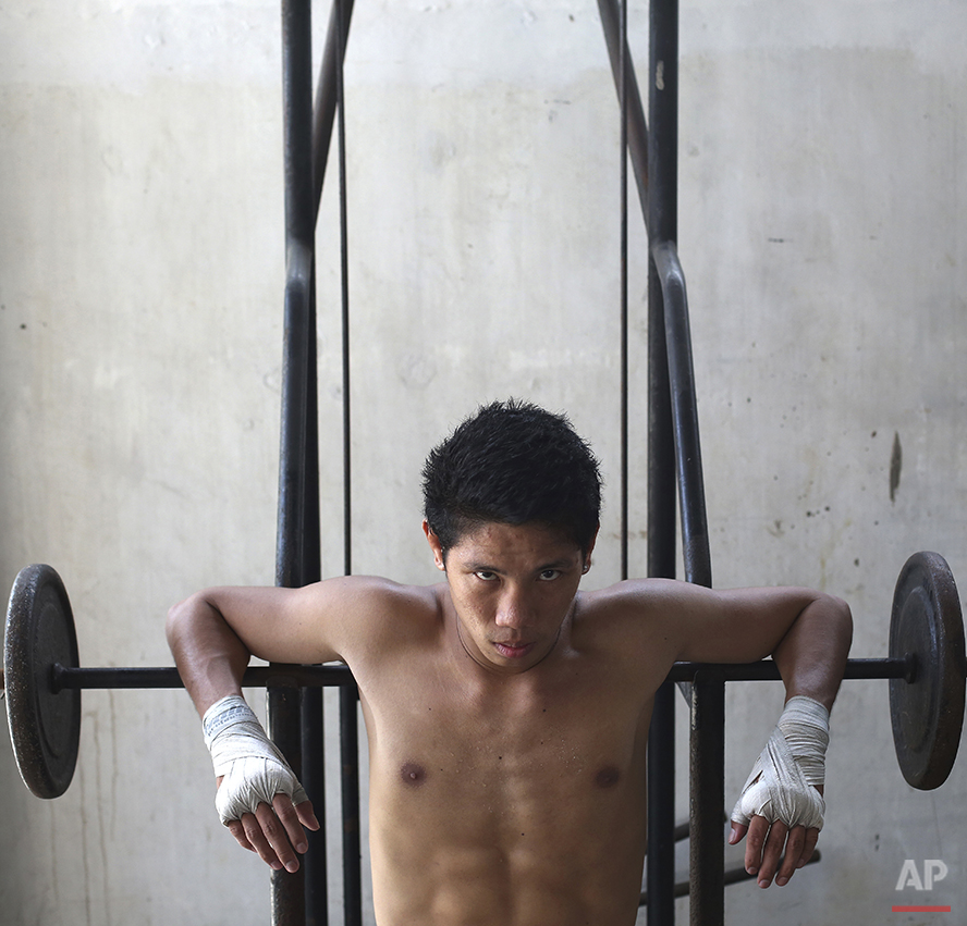 """In this April 21, 2015, photo, Filipino boxer, Joemarie Noynay, 19, poses inside a boxing gym in suburban Paranaque, south of Manila, Philippines. Noynay, who has won eight fights in the super bantamweight division, said, """"I sometimes think of the hardships, but I tell myself, if Pacquiao can do it, I can do it, too.... I just need to train hard and pray to the Lord to realize my dreams and the dreams of my family."""" Manny Pacquiao's rise from crushing poverty to global fame and fortune has inspired a whole generation of Filipino fighters, who look up to his legend as their dream and boxing as a ticket out of harsh lives and uncertainties. (AP Photo/Aaron Favila)"""