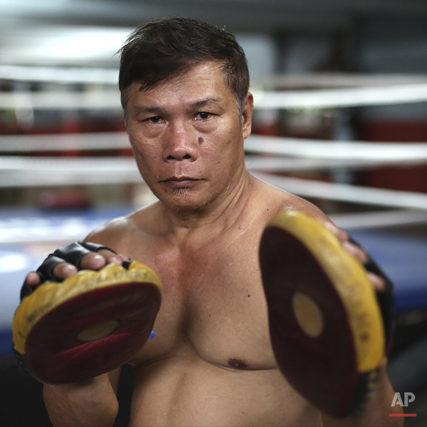 """In this April 21, 2015, photo, retired Filipino boxer and now trainer William Develos poses inside his boxing gym in suburban Paranaque, south of Manila, Philippines. Develos, 58, said,""""In training, you are already being made to suffer so that it will be easier for you when the time comes."""" Manny Pacquiao's rise from crushing poverty to global fame and fortune has inspired a whole generation of Filipino fighters, who look up to his legend as their dream and boxing as a ticket out of harsh lives and uncertainties. (AP Photo/Aaron Favila)"""