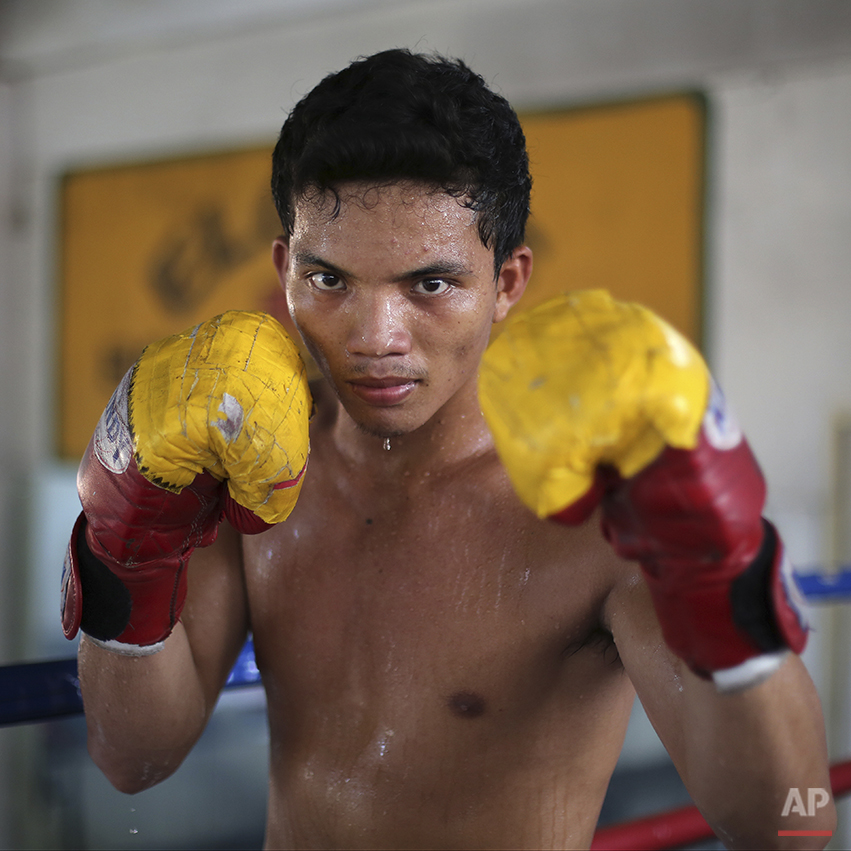 """In this April 21, 2015, photo, Filipino boxer Meljun Penapin poses with his worn-out boxing gloves inside a boxing gym in suburban Paranaque, south of Manila, Philippines. Penapin, 19, a boxer who has also been a barbecue vendor, a construction laborer, a bakery helper and a fisherman, said, """"I want to be a champion like Pacquiao... I was thinking that maybe I will be lucky. With such a hard life, maybe I will find my way of living here."""" Manny Pacquiao's rise from crushing poverty to global fame and fortune has inspired a whole generation of Filipino fighters, who look up to his legend as their dream and boxing as a ticket out of harsh lives and uncertainties. (AP Photo/Aaron Favila)"""