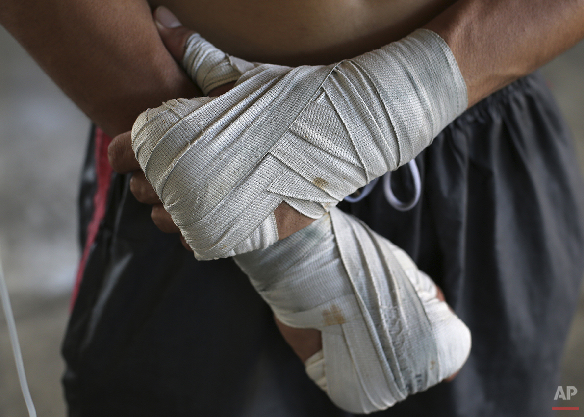 In this April 22, 2015, photo, a Filipino boxer waits for his turn to spar during training at a boxing gym in suburban Paranaque, south of Manila, Philippines. Many young boxers remain hopeful, despite the long odds, thousands of body blows and dreams of rival boxers that stand in their way.  (AP Photo/Aaron Favila)