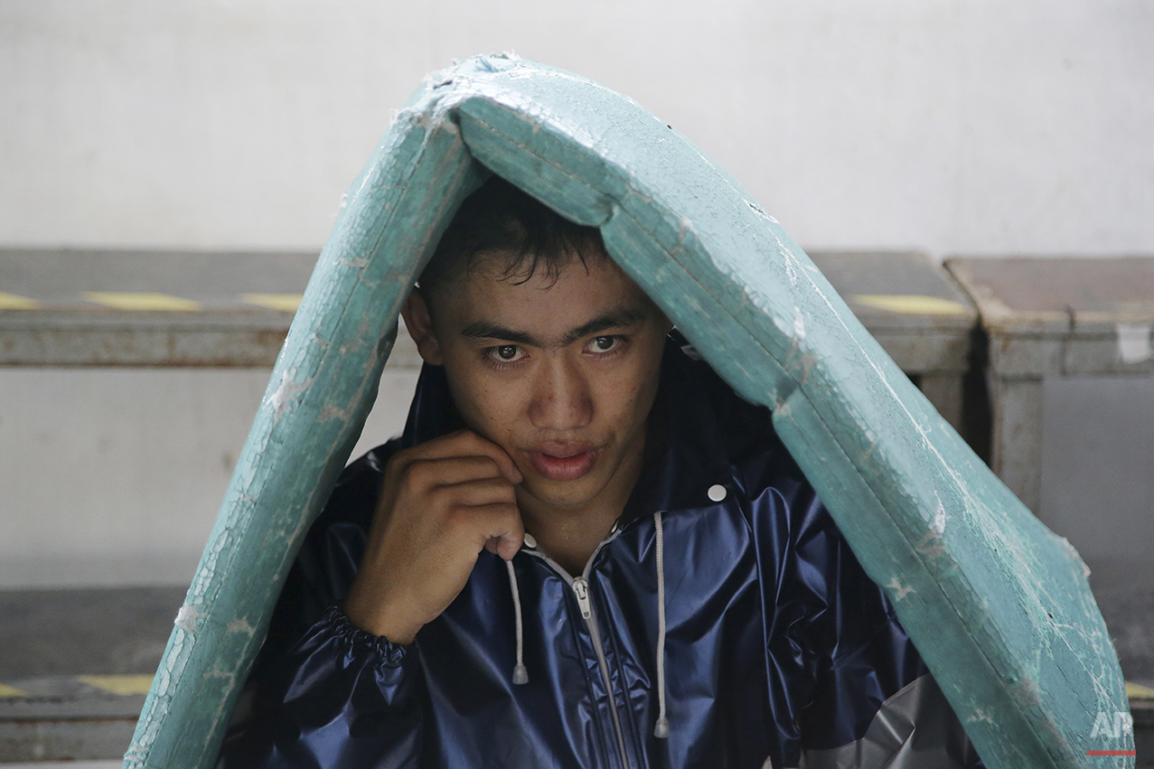 In this April 22, 2015, photo, a Filipino boxer wears a jacket as he sits underneath a mat to help him make weight for his upcoming bout at a boxing gym in suburban Paranaque, south of Manila, Philippines on Wednesday, April 22, 2015. Manny Pacquiao's rise from crushing poverty to global fame and fortune has inspired a whole generation of Filipino fighters, who look up to his legend as their dream and boxing as a ticket out of harsh lives and uncertainties. (AP Photo/Aaron Favila)