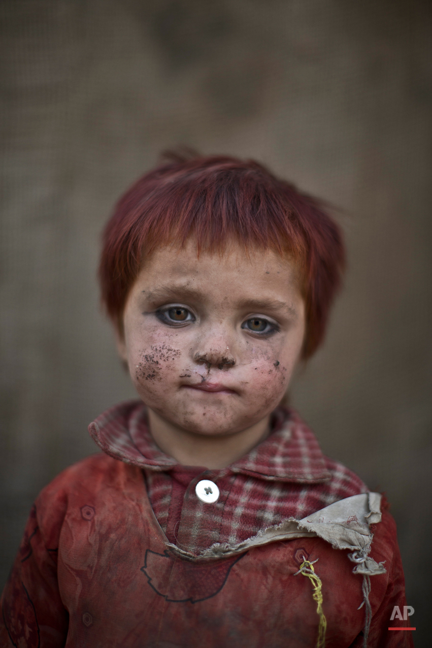 In this Friday, Jan. 24, 2014 photo, Afghan refugee girl, Gul Bibi Shamra, 3, poses for a picture, while playing with other children in a slum on the outskirts of Islamabad, Pakistan. (AP Photo/Muhammed Muheisen)