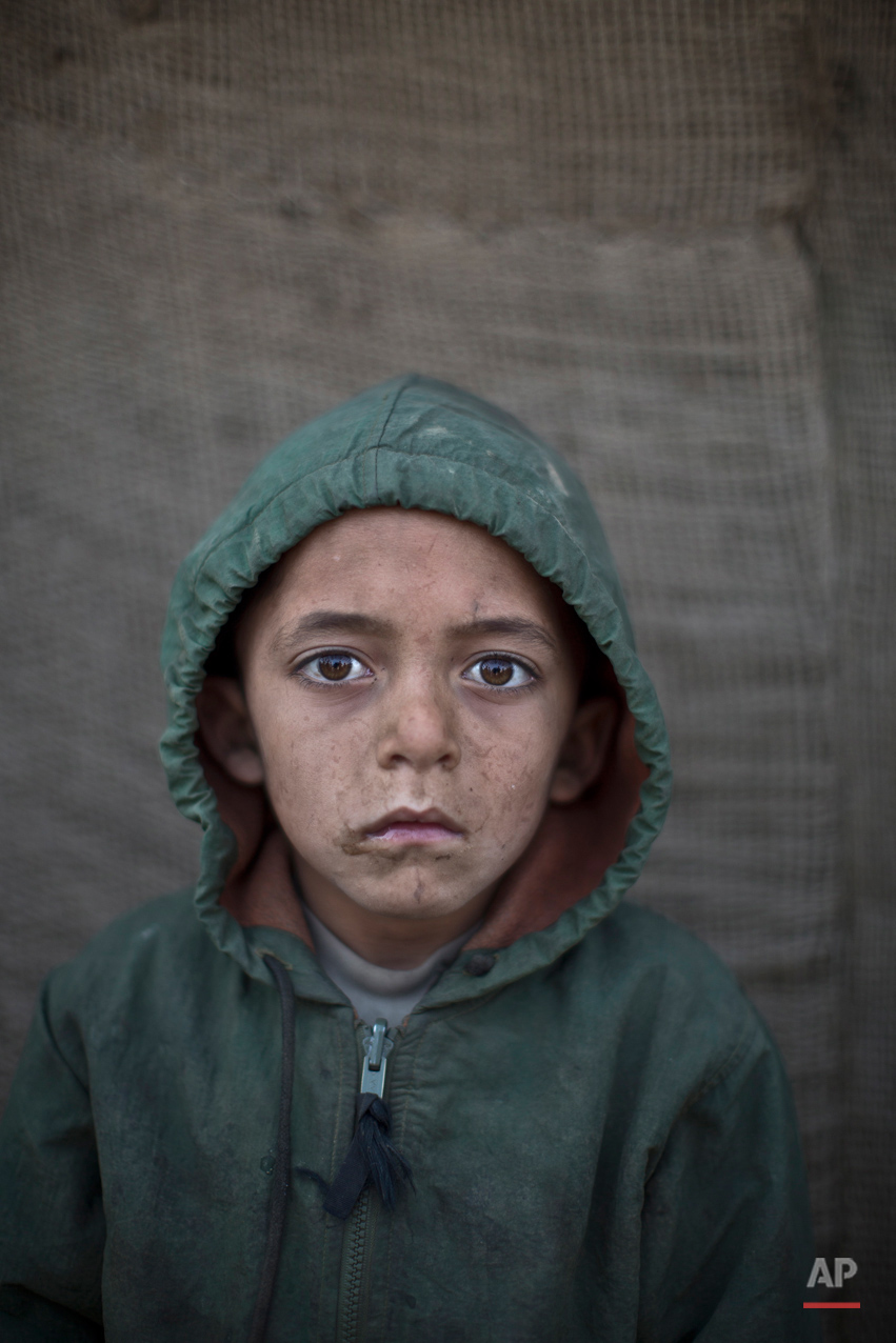 In this Saturday, Jan. 25, 2014, photo, Afghan refugee boy, Waheed Wazir, 6, poses for a picture, while playing with other children in a slum on the outskirts of Islamabad, Pakistan.  (AP Photo/Muhammed Muheisen)