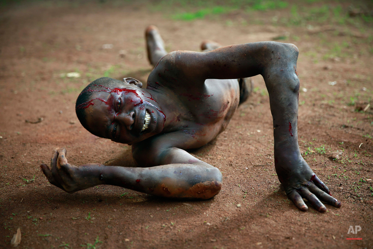 "Kevin, a man accused of being a thief by civil servants at the Work Inspection office, lays in pain after being attacked by a man with a machete and sticks,  in plain view of others, in Bangui, Central African Republic, Friday, April 18, 2014. Foreign journalists intervened and stopped the beating, as the crowd shouted ""he is a thief, he must die."" (AP Photo/Jerome Delay)"