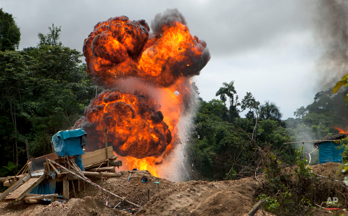 In this Wednesday, April 30, 2014 photo, gasoline used for illegal mining burns as it is destroyed by authorities in the Huepetuhe district of Peru's Madre de Dios region. (AP Photo/Rodrigo Abd)