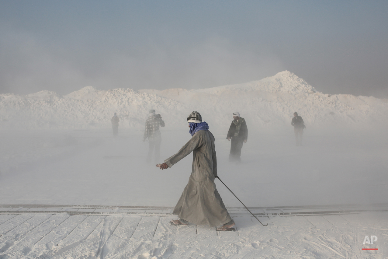 In this Wednesday, March 18, 2015 photo, limestone quarry workers walk through a cloud of dust spewed into the air by rotor blades of the stone-cutting machinery in the desert of Minya, southern Egypt. (AP Photo/Mosa'ab Elshamy)