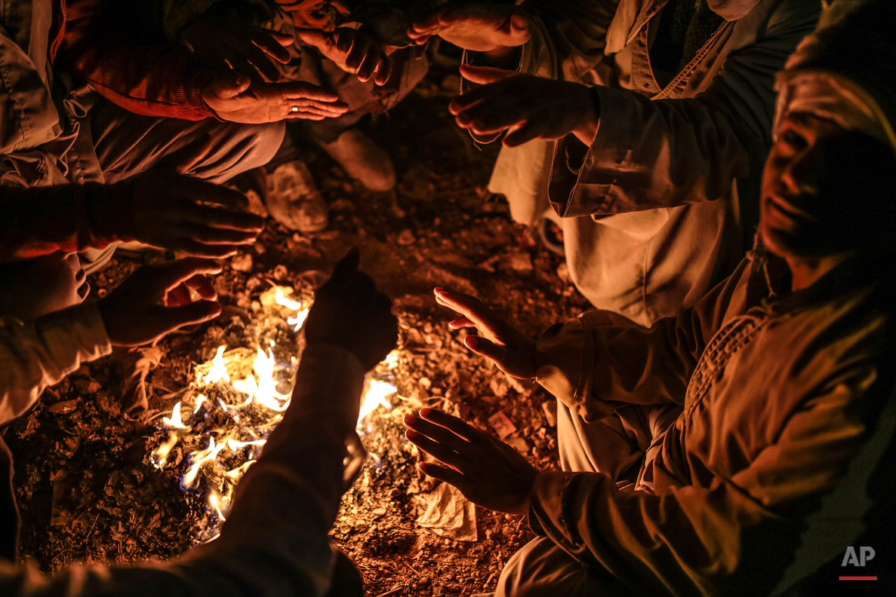 In this Wednesday, March 18, 2015 photo, quarry workers try to keep themselves warm around a bonfire as they wait for work after dawn in Shurafa village, Minya, southern Egypt. (AP Photo/Mosa'ab Elshamy)