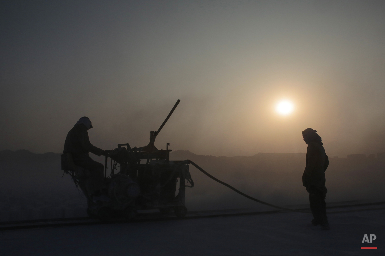In this Wednesday, March 18, 2015 photo, quarry workers use machinery with sharp rotor blades to cut through limestone pits in the desert of Minya, southern Egypt. Quarry work is considered one of the most dangerous and deadly jobs in the country, carrying a high risk of amputation, electrocution and various respiratory and skin diseases. (AP Photo/Mosa'ab Elshamy)