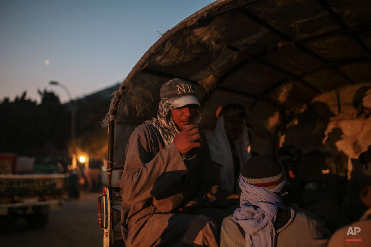 In this Wednesday, March 18, 2015 photo, a quarry worker keeps warm after dawn by drinking tea as he and others are transported in pick-up trucks to work in Minya, southern Egypt. The quarries are the main employers in the province, some 300 kilometers (180 miles) south of Cairo. (AP Photo/Mosa'ab Elshamy)