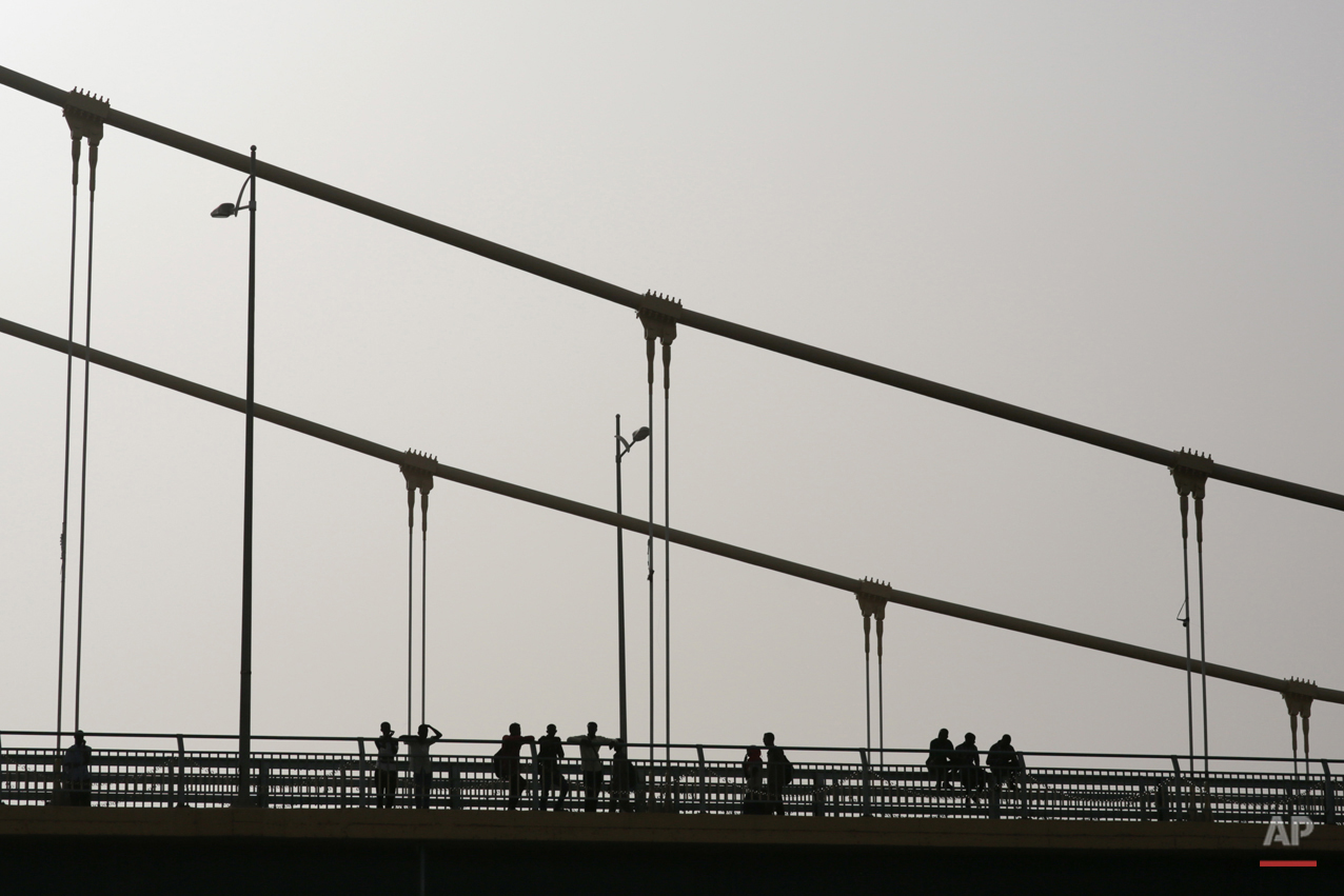 In this Saturday, April 11, 2015 photo, Sudanese youth relax on a bridge during sunset in Khartoum, Sudan. Nearly 13 million people are registered to vote for president and the 450-member legislative council starting Monday. Some 11,000 polling centers will be open through Wednesday, and results are expected on April 27. (AP Photo/Mosa'ab Elshamy)