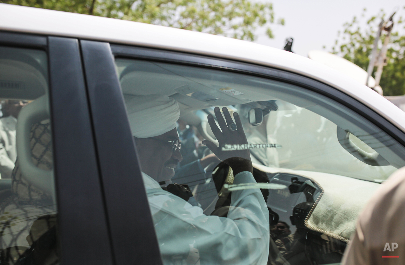 President Omar al-Bashir waves from his car outside a polling site after casting his ballot on the first day of presidential and legislative elections, in Khartoum, Sudan, Monday, April 13, 2015. Sudan began voting Monday in an election expected to be won by al-Bashir, who has ruled Sudan unchallenged for 25 years. (AP Photo/Mosa'ab Elshamy)
