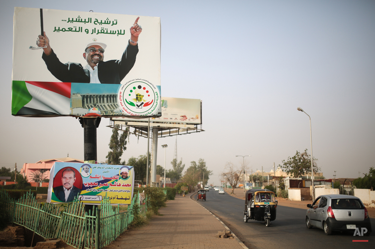 """In this Saturday, April 11, 2015 photo, vehicles drive past an election campaign banner in support of President Omar al-Bashir, in Omdurman, Sudan, that reads """"Nominating al-Bashir, for stability and reconstruction."""" Sudanís President Omar al-Bashir, the worldís only sitting leader wanted on genocide charges, is expected to win a landslide victory in elections this week, extending a 25-year reign in which the country has endured multiple insurgencies and the secession of the oil-rich south.(AP Photo/Mosa'ab Elshamy)"""