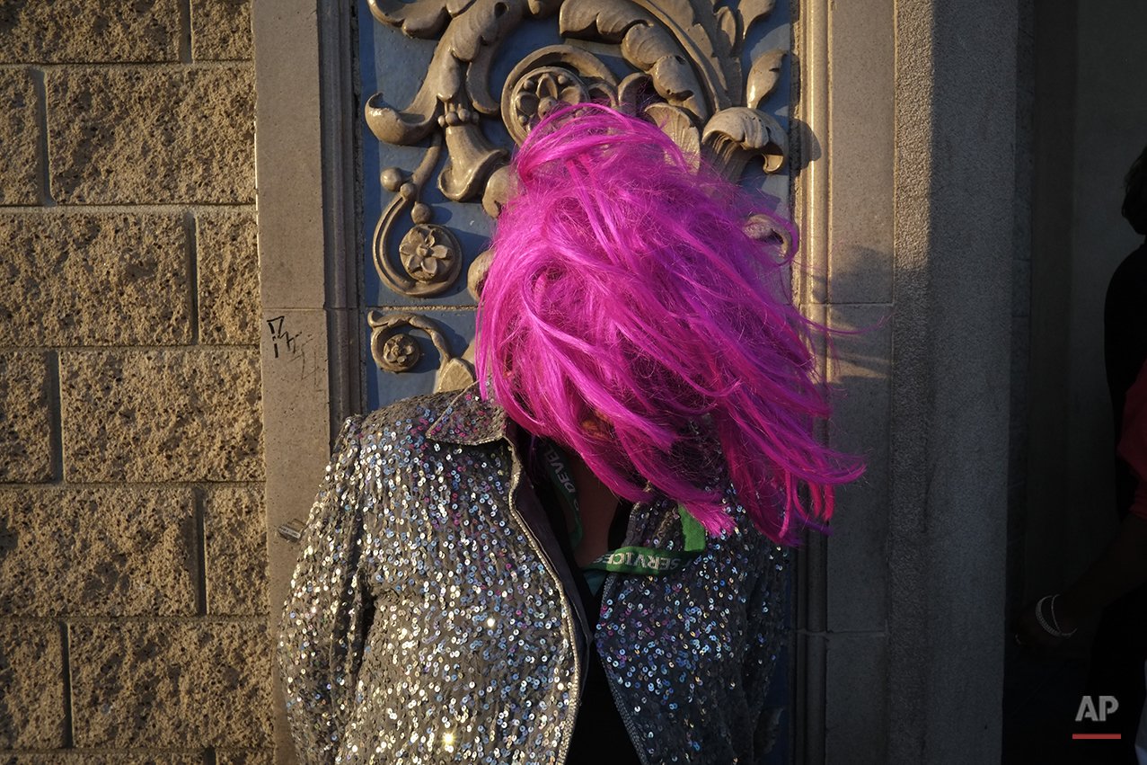 A homeless woman wears a wig while waiting for the start of a karaoke night outside a church in the Skid Row area of Los Angeles, Wednesday, May 15, 2013. (AP Photo/Jae C. Hong)