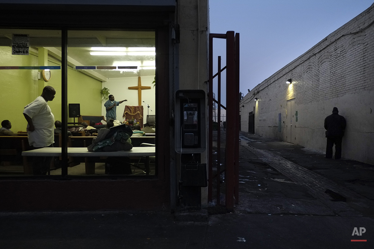 Pastor Emmanuel Okoli, standing next to a cross, gives a sermon to homeless people at Outreach Mission Center as a man, right, urinates in an alley in the Skid Row area of Los Angeles, Thursday, March 21, 2013. The area, originally agricultural until the 1870s when railroads first entered Los Angeles, has maintained a transient nature through the years from the influxes of short-term workers, migrants fleeing economic hardship during the Great Depression, military personnel during World War II and the Vietnam conflict, and low-skilled workers with limited transportation options who need to remain close to the city's core, according to the Los Angeles Chamber of Commerce. (AP Photo/Jae C. Hong)