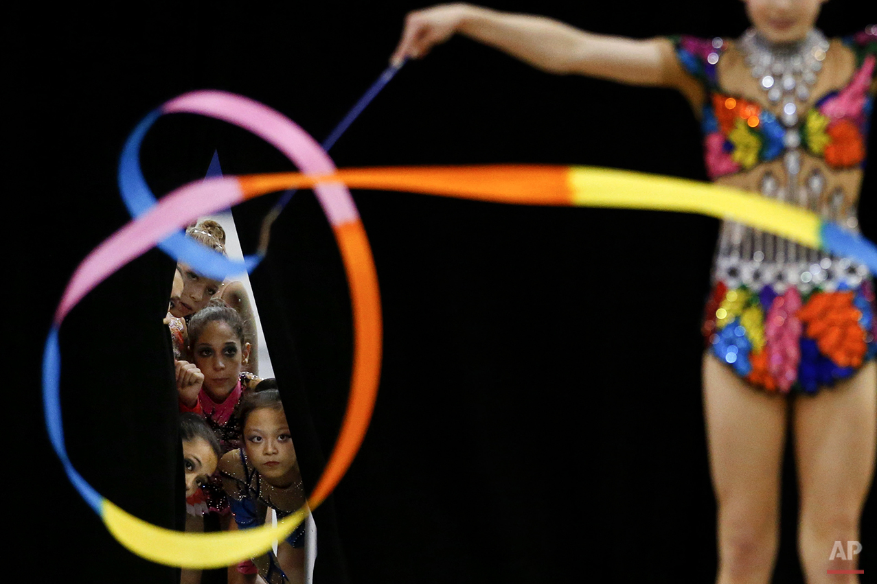 Members of the junior national team watch Jazzy Kerber, foreground, compete during the rhythmic all-around finals at the USA Gymnastics Championships in San Jose, Calif., Wednesday, June 27, 2012. (AP Photo/Jae C. Hong)