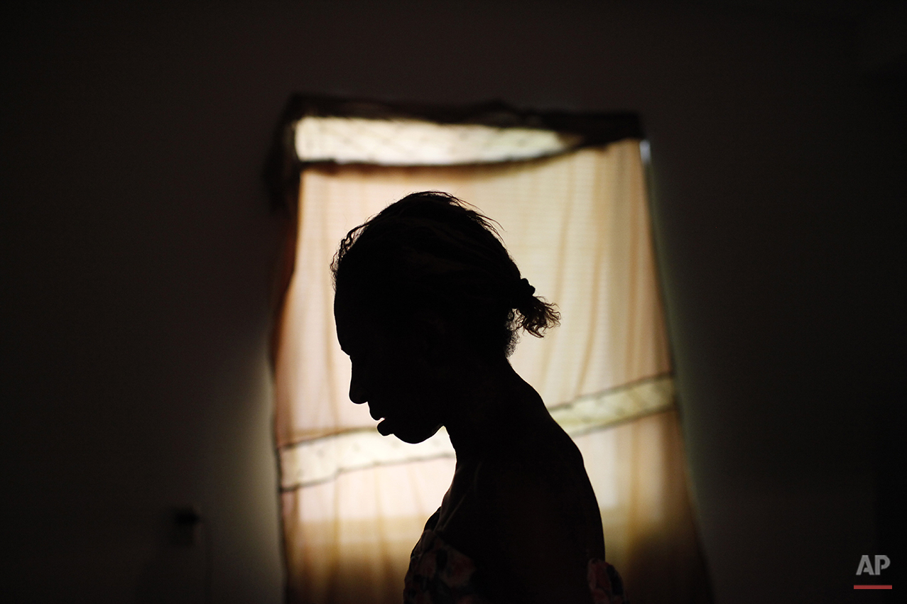 Sheila Nichols, 55, is silhouetted as she stands in room at the Charles Cobb Apartments in Los Angeles, Monday, July 19, 2010. After two decades living on the streets of Skid Row, Nichols was dying. Her body had wasted away to 61 pounds, ravaged by a heavy-duty crack cocaine addiction, hepatitis, HIV, and late-stage syphilis. Nichols was rescued by Project 50, a pilot program to get the 50 people most likely to die if they remained homeless into housing, medical care and social services. (AP Photo/Jae C. Hong)
