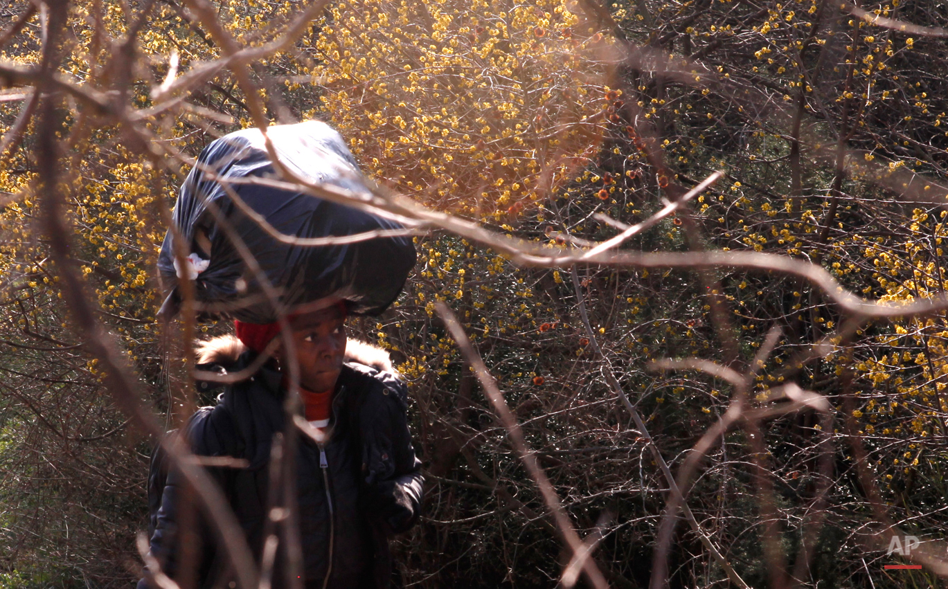 In this Saturday, Feb. 28, 2015 photo Sandrine from Cameroon carries her belongings on her head on her way to the Greek-Macedonian border near the town of Polikastro, Greece.  The tide of hopeful migrants pours through the vulnerable 'back-door' countries in the hope of entering the 28-nation European Union, and although most people don't make it, the human tide continues to grow, according to Frontex, the EU agency that helps governments police the blocís leaky frontiers. (AP Photo/Dalton Bennett)