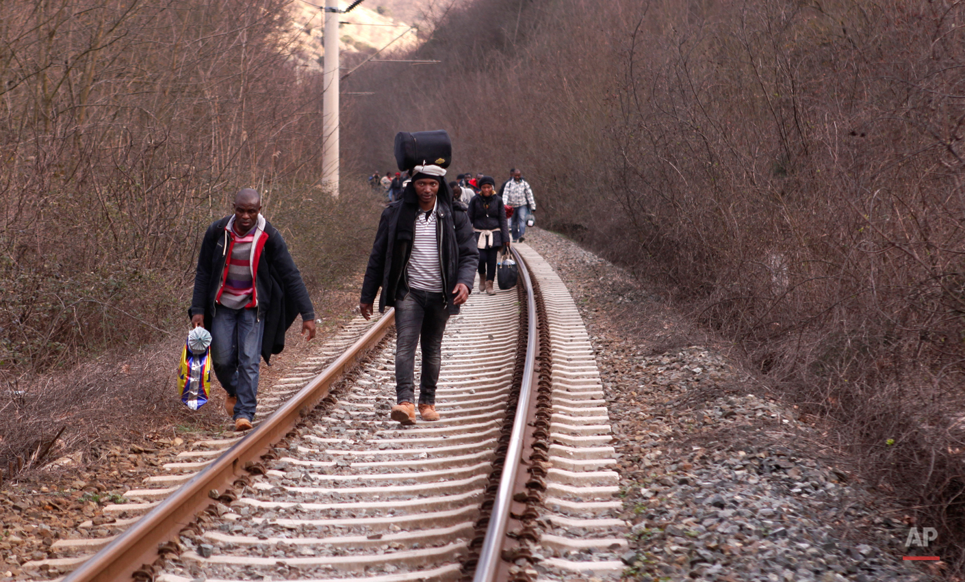 In this Saturday, Feb. 28, 2015 photo West African migrants walk on train tracks on their way towards the border with Macedonia near the town of Evzonoi, Greece.  The tide of hopeful migrants pours through the vulnerable 'back-door' countries in the hope of entering the 28-nation European Union, and although most people don't make it, the human tide continues to grow, according to Frontex, the EU agency that helps governments police the blocís leaky frontiers. (AP Photo/Dalton Bennett)