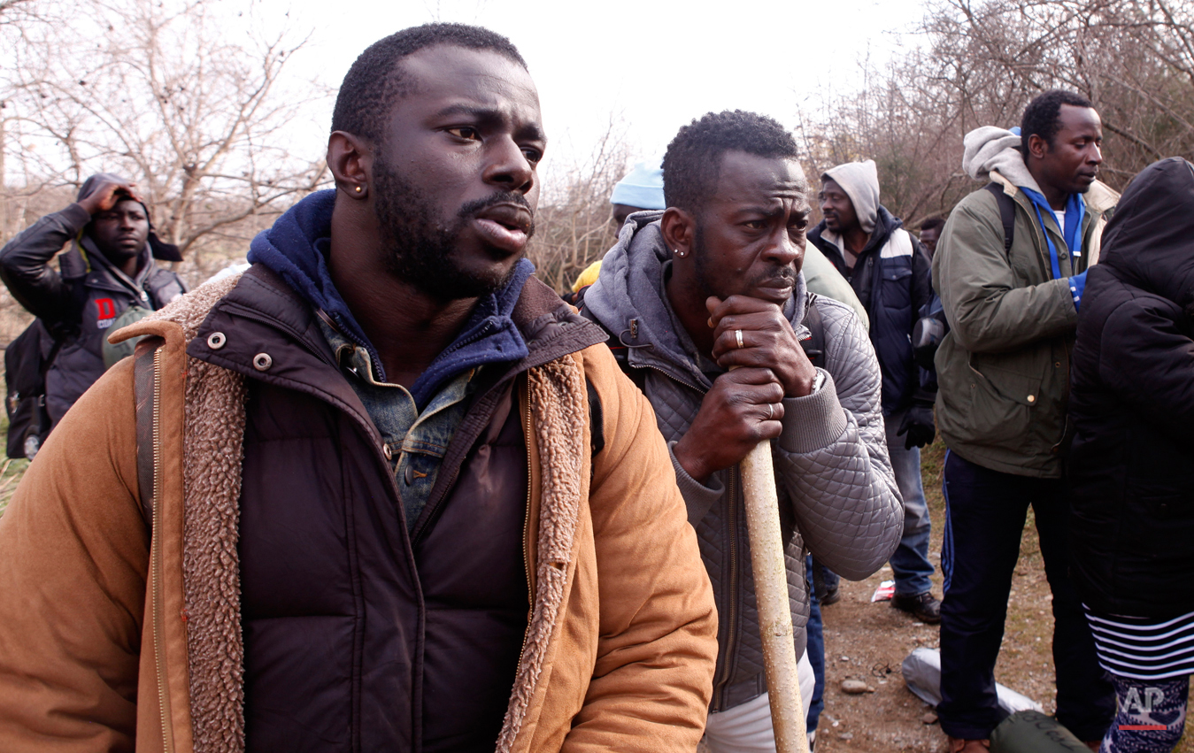 In this Saturday, Feb. 28, 2015 photo Jean Leblanc, left, and Antoine Sannick of Ivory Coast rest on their way to the Greek-Macedonian border near the town of Polikastro, Greece.  The tide of hopeful migrants pours through the vulnerable 'back-door' countries in the hope of entering the 28-nation European Union, and although most people don't make it, the human tide continues to grow, according to Frontex, the EU agency that helps governments police the blocís leaky frontiers. (AP Photo/Dalton Bennett)