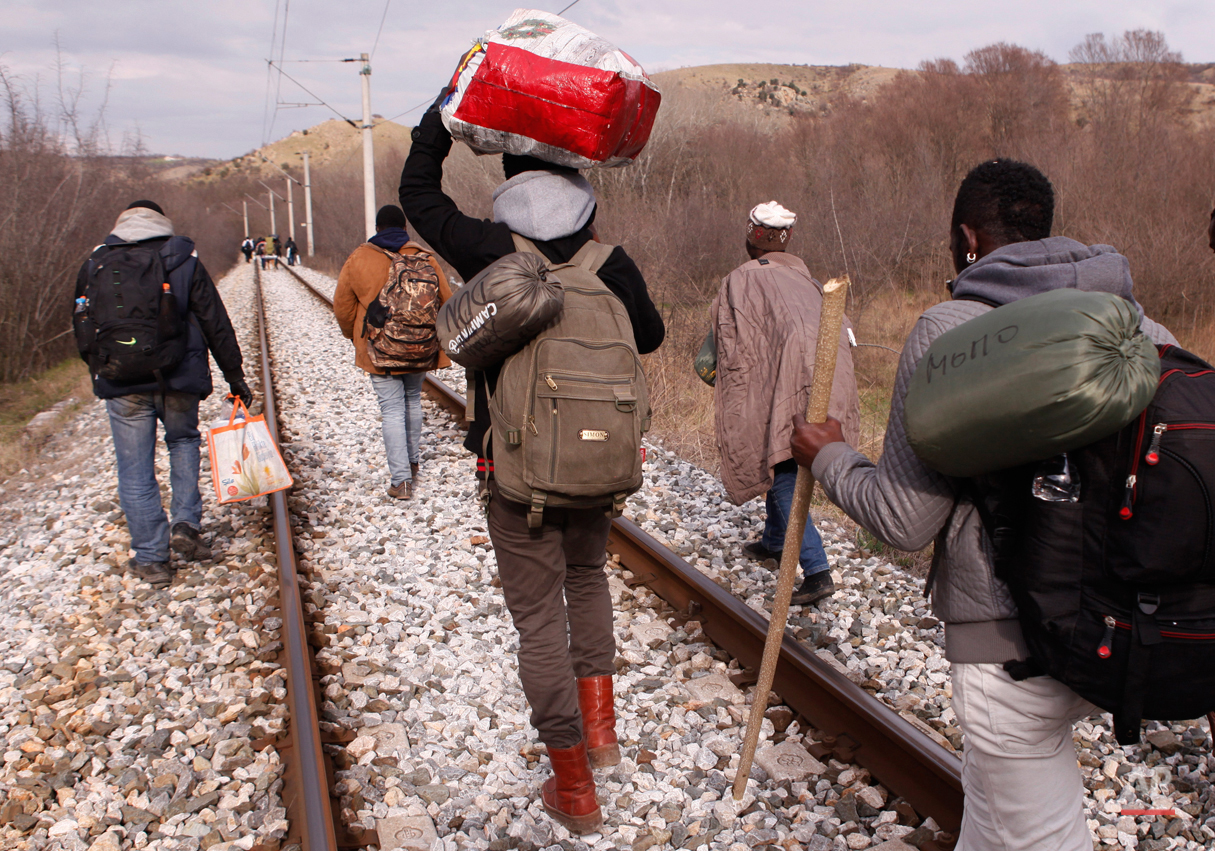 In this Saturday, Feb. 28, 2015 photo West African migrants walk on train tracks on their way to the Greek-Macedonian border near the town of Evzonoi, Greece.  The tide of hopeful migrants pours through the vulnerable 'back-door' countries in the hope of entering the 28-nation European Union, and although most people don't make it, the human tide continues to grow, according to Frontex, the EU agency that helps governments police the blocís leaky frontiers. (AP Photo/Dalton Bennett)