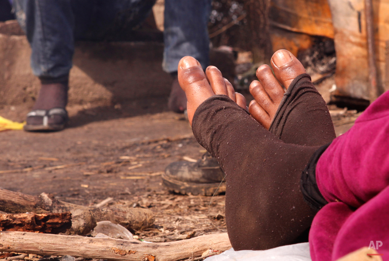 In this Sunday, March 1, 2015 photo a West African migrant rests in a makeshift camp near the town of Evzonoi, Greece, before crossing the border to Macedonia.  The tide of hopeful migrants pours through the vulnerable 'back-door' countries in the hope of entering the 28-nation European Union, and although most people don't make it, the human tide continues to grow, according to Frontex, the EU agency that helps governments police the blocís leaky frontiers. (AP Photo/Dalton Bennett)