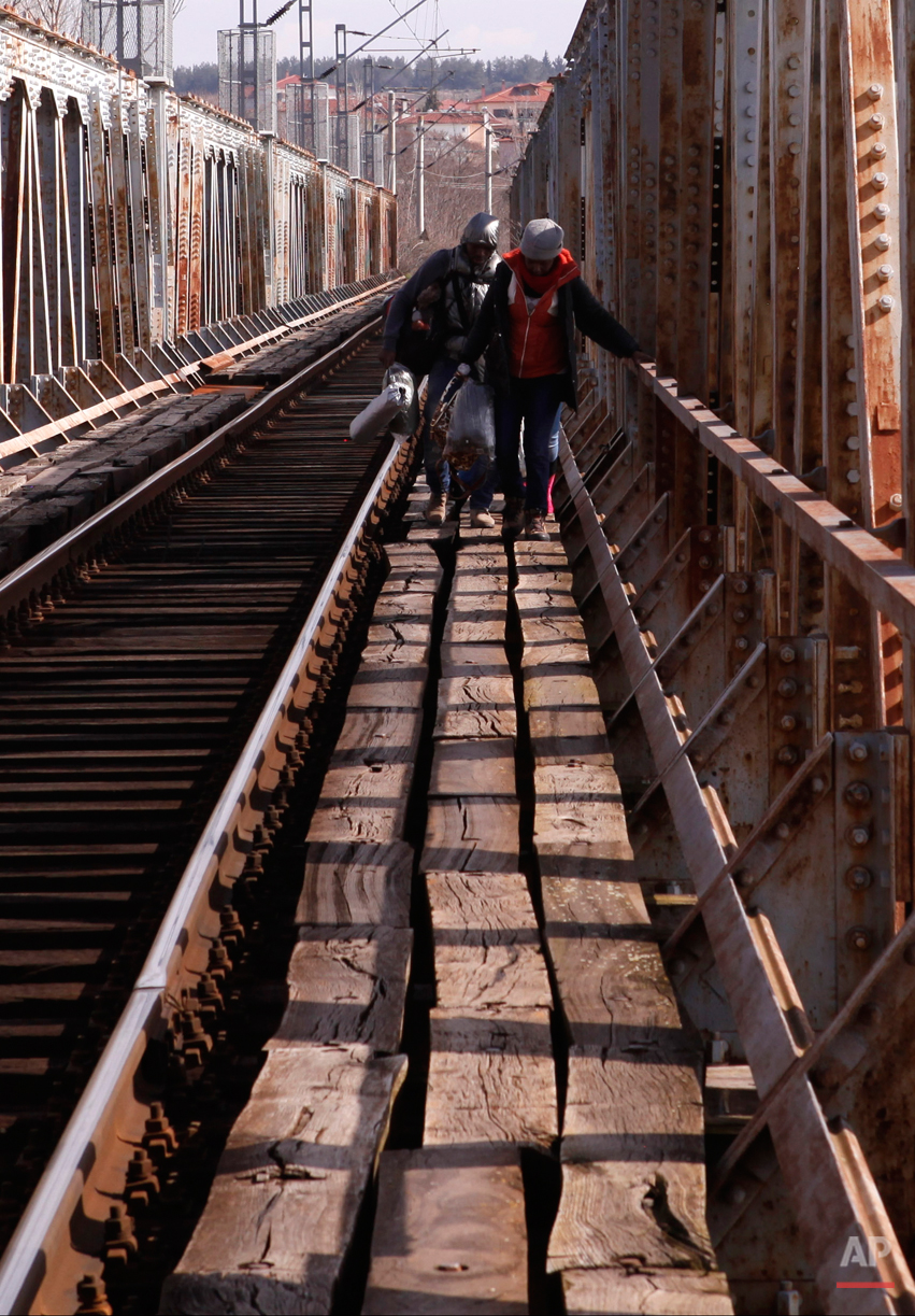 In this Saturday, Feb. 28, 2015 photo Migrants cross a railway bridge on their way to the Greek-Macedonian border near Polikastro, Greece.  The tide of hopeful migrants pours through the vulnerable 'back-door' countries in the hope of entering the 28-nation European Union, and although most people don't make it, the human tide continues to grow, according to Frontex, the EU agency that helps governments police the blocís leaky frontiers. (AP Photo/Dalton Bennett)