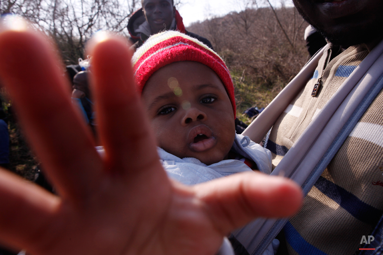 In this Saturday, Feb. 28, 2015 photo 10-months-old migrant Christian Djeukam reaches out to the lens of the photographer as he sits in a baby carrier near the town of Evzonoi, Greece. The tide of hopeful migrants pours through the vulnerable 'back-door' countries in the hope of entering the 28-nation European Union, and although most people don't make it, the human tide continues to grow, according to Frontex, the EU agency that helps governments police the blocís leaky frontiers. (AP Photo/Dalton Bennett)