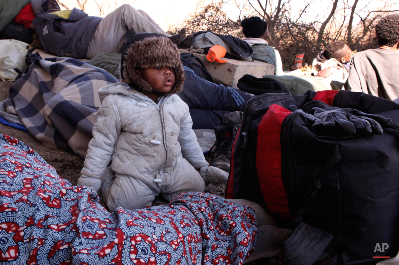 In this Tuesday, March 3, 2015 photo 10-months-old Christian Djeukam watches the rest of the group at during a stop under a freeway overpass near the village of Marvintsi, Macedonia.  The tide of hopeful migrants pours through the vulnerable 'back-door' countries in the hope of entering the 28-nation European Union, and although most people don't make it, the human tide continues to grow, according to Frontex, the EU agency that helps governments police the blocís leaky frontiers. (AP Photo/Dalton Bennett)