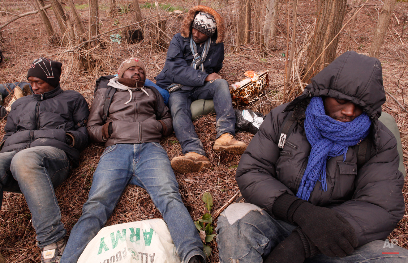 In this Friday, March 6, 2015 photo West African migrants sit exhausted after a night of heavy rain and hail that destroyed their tents near Gradsko, Macedonia.  The tide of hopeful migrants pours through the vulnerable 'back-door' countries in the hope of entering the 28-nation European Union, and although most people don't make it, the human tide continues to grow, according to Frontex, the EU agency that helps governments police the blocís leaky frontiers. (AP Photo/Dalton Bennett)