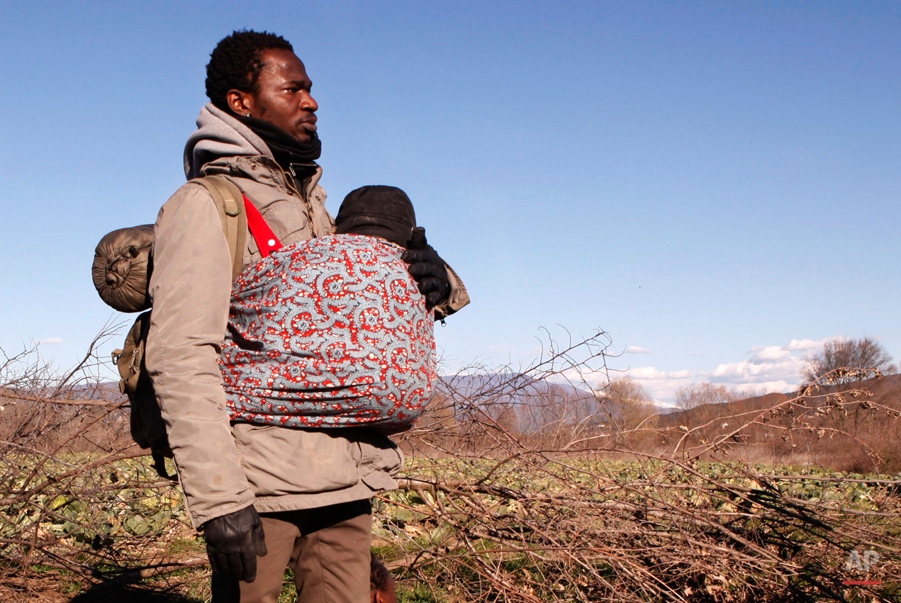 In this Tuesday, March 3, 2015 photo Jean-Paul Apetey of Ivory Coast helps carrying a baby near the village of Udovo, Macedonia.  The tide of hopeful migrants pours through the vulnerable 'back-door' countries in the hope of entering the 28-nation European Union, and although most people don't make it, the human tide continues to grow, according to Frontex, the EU agency that helps governments police the blocís leaky frontiers. (AP Photo/Dalton Bennett)