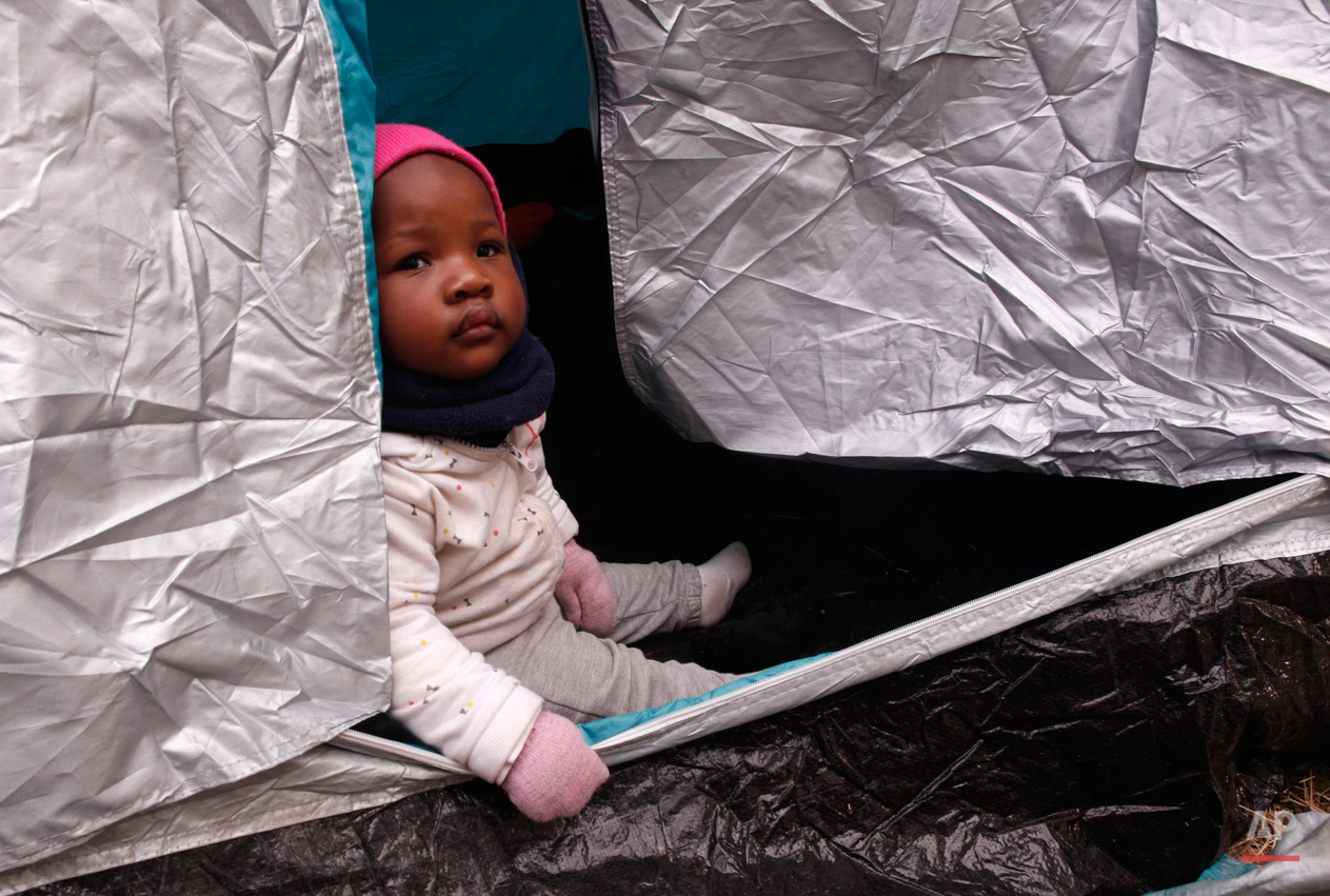 In this Monday, March 2, 2015 photo 10-months-old Kendra Koffi looks out of a tent near the town of Gevgelija, Macedonia, after crossing the border from Greece.  The tide of hopeful migrants pours through the vulnerable 'back-door' countries in the hope of entering the 28-nation European Union, and although most people don't make it, the human tide continues to grow, according to Frontex, the EU agency that helps governments police the blocís leaky frontiers. (AP Photo/Dalton Bennett)
