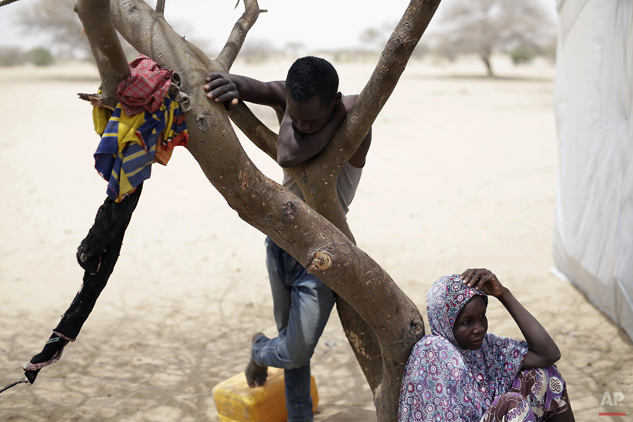 Nigerians who fled Boko Haram to Chad sit outside their tent at the Baga Sola refugee camp in Chad, Wednesday March 4, 2015. The camp, jointly run by the Chadian government and UNHCR, opened mid-January 2015 and hosts over 6000 refugees. Officials say that several thousand had arrived in Chad by the end of 2015 as Boko Haram intensified its attacks in the area. After the Baga massacre, another 15,000 came bringing the total now to about 18,000, Chadian authorities believe there are more than 2,000 others still trapped on islands, awaiting transport to the safety of a refugee camp though there are more arriving each day in one of the poorest countries on Earth. (AP Photo/Jerome Delay)